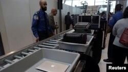 Bagasi dan laptop penumpang diperiksa melalui alat pemindai di bandara JFK, New York (foto: ilustrasi).