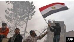 Người biểu tình phất cờ trong khi đụng độ diễn ra bên ngoài trụ sở Bộ Nội vụ ở Cairo, ngày 6/2/2012