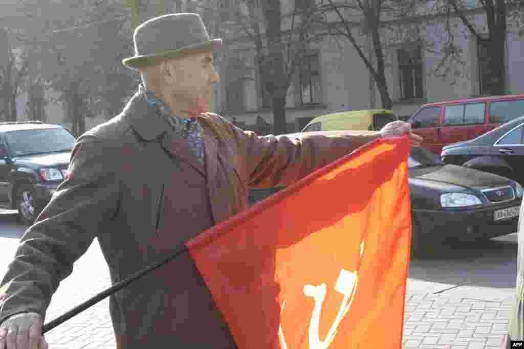 """На пути шествия """"Русского марша"""". Пенсионеры с красными флагами вышли на улицы требовать от правительства не сокращать социальные льготы малоимущим слоям населения."""