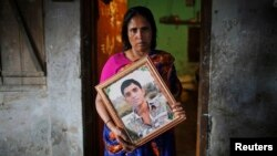 Fatema holds a picture of her son Nurul Karim as she poses for a photograph in front of her house in Savar, April 21, 2014. Fatema lost her son and her daugther Arifa, who were working at the Rana Plaza when it collapsed on April 24, 2013.