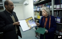 FILE - Nancy Hatch Dupree and her colleague show an archived paper of the Taliban regime during an interview with The Associated Press at the Afghanistan Center in Kabul University, Dec. 9, 2014.