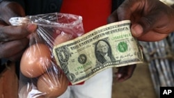 A man buys eggs using a U.S. one dollar bill at a market in Harare (File)