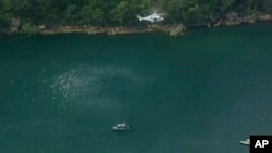 In this image made from a video, a search and rescue helicopter flies above search boats in Hawkesbury River, New South Wales, Australia, Dec. 31, 2017. A seaplane crashed into the river in Sydney.