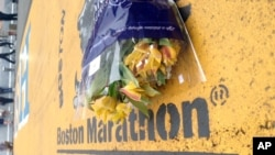 "Flowers rest at the finish line of the Boston Marathon after the verdict in the penalty phase of the trial of Marathon bomber Dzhokhar Tsarnaev, May 15, 2015, in Boston. Tsarnaev was sentenced to death by lethal injection in the 2013 attack. Robert Lorenz Hester Jr., arrested Feb. 21, 2017, in Kansas City, reportedly wanted to take part in an attack ""10 times more'' severe than the Boston Marathon bombing."