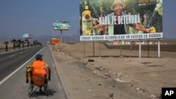 Jose Suarez, from Cucuta, Colombia, moves his wheelchair, decorated with a stuffed animal, along the Pan American Highway lined with billboards advertising rum, lottery and mixed nuts, on the south side of Lima, Peru, May 5, 2017.