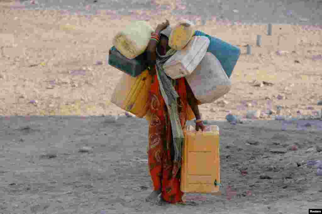 A girl carries cans to fill with drinking water at a camp for displaced people from the Red Sea port city of Hodeidah near Aden, Yemen.