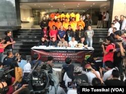 Humas Polda Metro Jaya Argo Yuwono (tengah) berbicara kepada wartawan seraya menunjukkan para tersangka dan sejumlah barang bukti demonstrasi ricuh 22 Mei. (VOA/Rio Tuasikal)