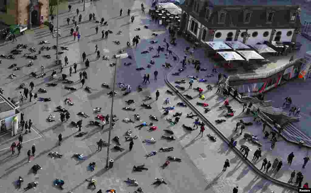 "People lay down in a pedestrian zone as part of an art project in remembrance of the 528 victims of the ""Katzbach"" Nazi concentration camp, in Frankfurt, Germany, Mar. 24, 2014. The inmates of the Katzbach concentration camp, a part of the former Adler industrial factory, were forced into a death march to the concentration camps of Buchenwald and Dachau on Mar. 24, 1945. Some 528 victims of Katzbach are buried at Frankfurt's central cemetery."