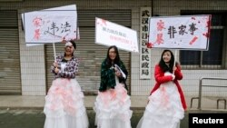 FILE - University students dressed as battered wives hold banners in front of an office of China's Civil Affairs department, where local people register for marriage, in protest of domestic violence, during the International Day for the Elimination of Vio