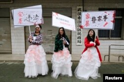 FILE - University students dressed as battered wives hold banners in front of an office of China's Civil Affairs department, where local people register for marriage, in protest of domestic violence, during the International Day for the Elimination of Violence against Women, in Hubei province, Nov. 25, 2012.
