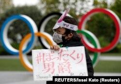 Seorang pengunjuk rasa anti-Olimpiade berdemo di depan monumen cincin Olimpiade, di Tokyo, 18 Mei 2021. (Foto: Reuters)