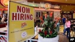 美国劳工部3月10日报告称美国2月份增加了23万5千个就业职位。 佛罗里达州迈阿密的一家餐馆竖立看板招募员工。(档案图片)。