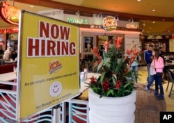 FILE - A restaurant posts a sign indicating they are hiring, in Miami, Florida, Feb. 9, 2016.