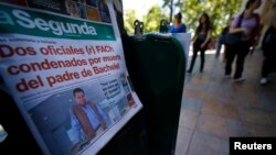 """An afternoon edition of the """"La Segunda"""" newspaper, with its front page headline reading """"Two Air Force officers convicted of killing the father of Bachelet,"""" the latter referring to Chilean President Michelle Bachelet, is seen at a stand in downtown Santiago, Nov. 21, 2014."""