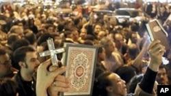 En Egypte des musulmans et des chrétiens lors d'une manifestation pour protester contre l'attaque d'une eglise copte à Alexandrie.