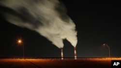 FILE - In this Jan. 19, 2012 file photo, smoke rises in this time exposure image from the stacks of the La Cygne Generating Station coal-fired power plant in La Cygne, Kansas.
