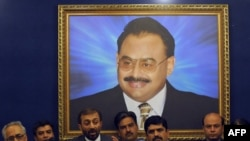 Leader of the Pakistani political party Muttahida Qaumi Movement (MQM), Farooq Sattar (3rd L), announces his parties decision to quit the coalition government in front of the portrait of MQM's self-exiled chief Altaf Hussain during a press conference in Karachi, June 27, 2011.