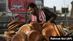An Afghan street vendor sells bread before the Iftar meal that breaks the fast during the Muslim holy month of Ramadan, Kabul, Afghanistan, June 5, 2018.