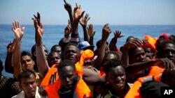 Des migrants et réfugiés reçoivent des gilets de sauvetage de l'ONG espagnole Proactiva Open Arms, après avoir été secourus alors qu'ils dérivaient à bord d'un canot pneumatique en mer Méditerranée, au large de Sabratha, Libye, 15 juin 2017.