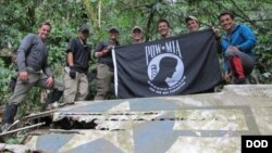 Anggota dari Defense POW / Badan Akuntansi MIA (DPAA), memegang bendera POW / MIA di atas sepotong puing logam dalam misi penyelidikan DPAA dekat desa Bhismaknagar, Arunachal Pradesh, India, 2 Desember 2016. (Foto: dok).