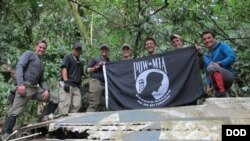 Members from Defense POW/MIA Accounting Agency (DPAA), hold the POW/MIA flag above a piece of metallic debris during a DPAA investigation mission near Bhismaknagar Village, Arunachal Pradesh, India, Dec. 02, 2016.