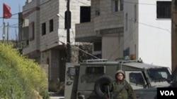 Tentara Israel berpatroli di perkampungan Awarta, Sabtu (12/3) setelah sebuah keluarga dibunuh di dekat Itamar, salah satu pemukiman Yahudi di Tepi Barat.