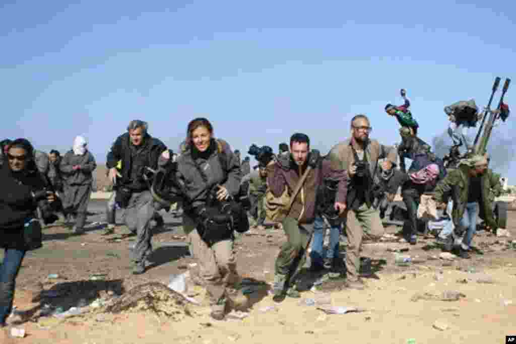 Jornalistas e fotógrafos fogem durante o bombardeamento, pela força aérea líbia, do terminal petrolífero de Ras Lanuf