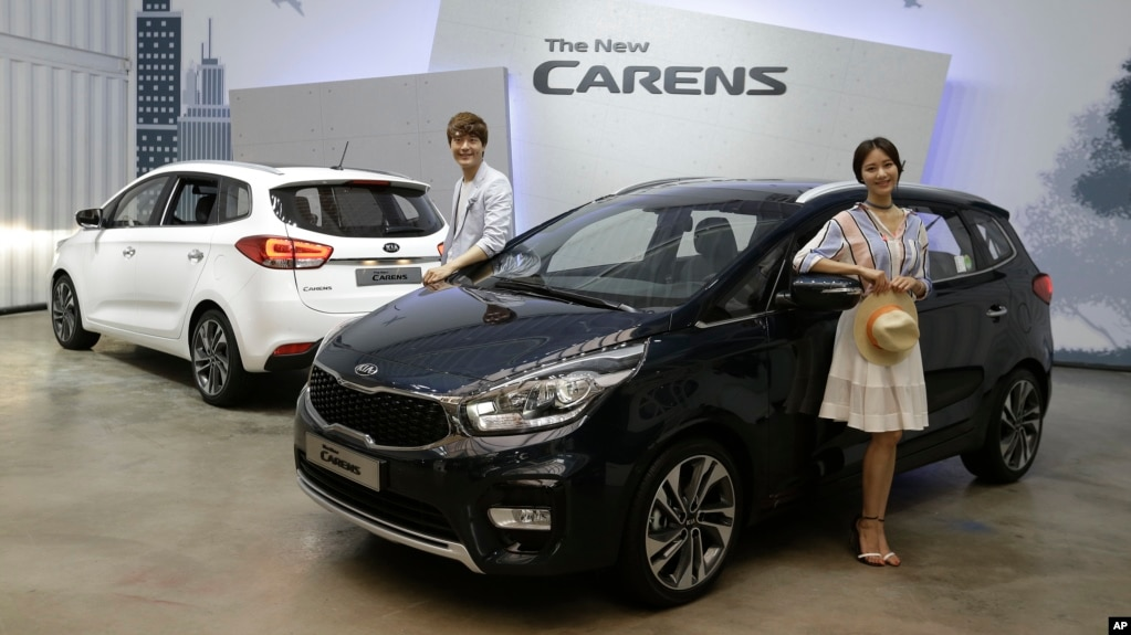 FILE - Models pose next to Kia Motors Corp.'s New Carens during its
