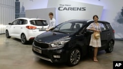 FILE - Models pose next to Kia Motors Corp.'s New Carens during its unveiling in Seoul, South Korea, July 26, 2016.