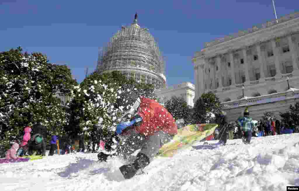 A boy crashes his sled on a hill at the U.S. Capitol after a major winter storm swept over Washington, D.C.  The National Weather Service said 17.8 inches (45.2 cm) fell in Washington, tying as the fourth-largest snowfall in the city's history.
