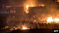 Des migrants sont évacués après un géant incendie dans le camp de Grande-Synthe dans la ville de Dunkirk, 10 avril 2017.