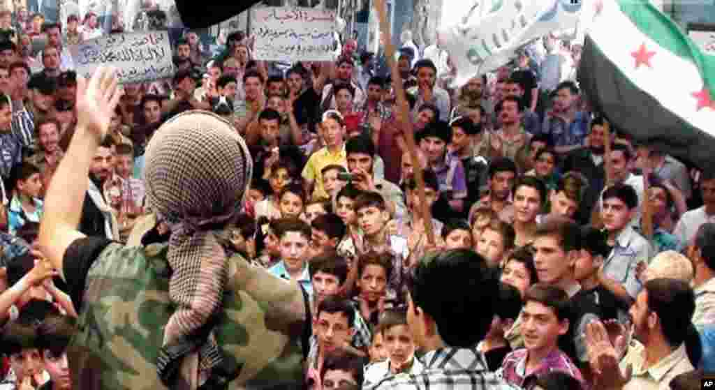 In this citizen journalism image provided by the United media office of Arbeen, a Syrian protester chants slogans during a demonstration in Arbeen, a suburb of Damascus, Sept. 13, 2013.
