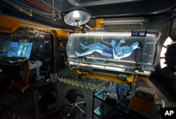 In this April 29, 2017 photo, park guests see a Na'vi in a science lab while in the queue for the Avatar Flight of Passage ride at Pandora-World of Avatar land attraction in Disney's Animal Kingdom theme park at Walt Disney World in Lake Buena Vista, Florida.