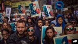 19일 뉴욕 타임스스퀘어에 모인 군중이 이슬람계 미국인을 상징하는 포스터를 든 채 도널드 트럼프 대통령의 이민정책에 항의하는 시위를 벌이고 있다.