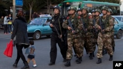 Policemen and paramilitary policemen patrol a street near the Kunming Railway Station, where more than 10 assailants slashed scores of people with knives Saturday evening, in Kunming, in southwestern China's Yunnan province, March 3, 2014.