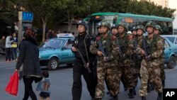 Policemen and paramilitary policemen patrol a street near the Kunming Railway Station, where the knife attack took place.