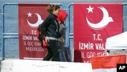 Un policier escorte un immigrant irrégulier dans un port turc, le 4 avril 2016.