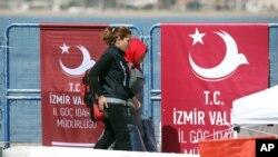 Polisi Turki mengawal migran dari kapal yang berasal dari Chios, Yunani dan berlabuh di Dikili, Turki, 4 April 20116 (Foto: dok)