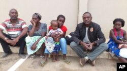 Correspondente da VOA (2º à direita) com a família de Alves Kamulingue, incluindo o seu primo, a sua mãe, a esposa, Elisa, o filho de 2 anos, e Tetê, esposa de Isaías Cassule.