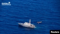 A Libyan coast guard vessel is pictured next to a migrant craft at sea, near Libya, June 5, 2019. A wooden boat carrying at least 22 African migrants was intercepted June 7 north of the Bouri offshore oil field, around 105 kilometers (65 miles) from Tripo