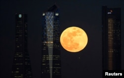A supermoon rises in between four towers in a skyscrapers area in Madrid, Spain, Jan. 31, 2018.