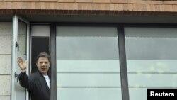 El presidente Juan Manuel Santos saluda desde la ventana del hospital donde fue intervenido.