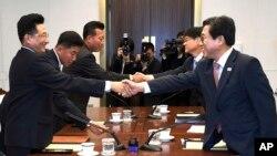 Trong tấm ảnh do Bộ Văn Hóa Thể Thao Hàn quốc cung cấp, trưởng phái bộ Hàn quốc Jeon Choong-ryul, phải, bắt tay với vị tương nhiệm Triều Tiên Won Kil U trong một cuộc gặp ở làng Bàn Môn Điếm, phía Nam khu vực phi quân sự chia cắt hai miền.