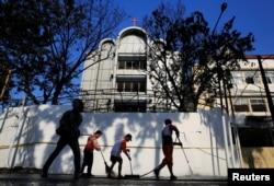 Beberapa orang mulai membersihkan bagian luar satu dari tiga gereja yang sehari sebelumnya diserang bom bunuh diri di Surabaya, 14 Mei 2018.