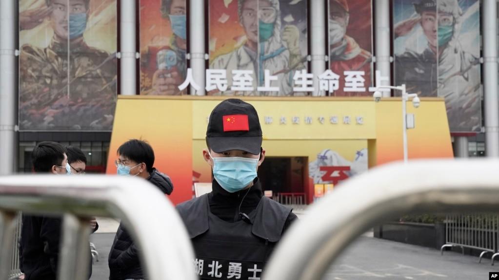 资料照片:一名保安人员在世卫组织团队抵达武汉后守卫在一处抗疫宣传展览的入口。(2021年1月30日)