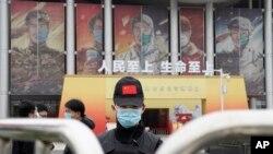 世界衛生組織團隊於 2021年1月30日星期六抵達中中國中部湖北省武漢市舉行的抗擊冠狀病毒展覽後,一名戴著口罩和帶有中國國旗的帽子的保安人員守衛入口。
