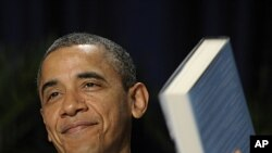 President Barack Obama holds up a book that he was given by author and keynote speaker Eric Metaxas, at the National Prayer Breakfast in Washington, February 2, 2012.
