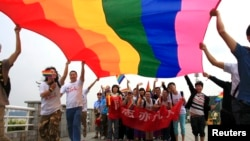 "Activists march during a demonstration to mark the International Day Against Homophobia and Transphobia in Changsha, May 17, 2013. The banner reads, ""Homosexsuals are also ordinary people""."