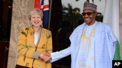 British Prime Minister Theresa May, left, is welcomed by Nigeria's President Muhammadu Buhari, at the Presidential palace in Abuja, Nigeria, Aug. 29, 2018.