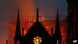 FILE - Flames and smoke rise from Notre Dame cathedral as it burns in Paris, Monday, April 15, 2019. (AP Photo/Thibault Camus)